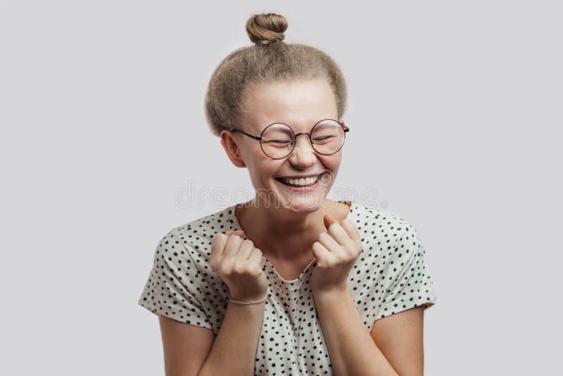 De mooie emotionele dame in vrijetijdskleding heft indient vuisten en het glimlachen op stock foto