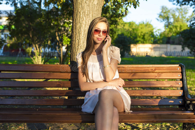 De mooie emotionele donkerbruine meisje het lachen de zomerglazen van het telefoonpark roze kleding, genieten van uw vakantie in  stock foto's