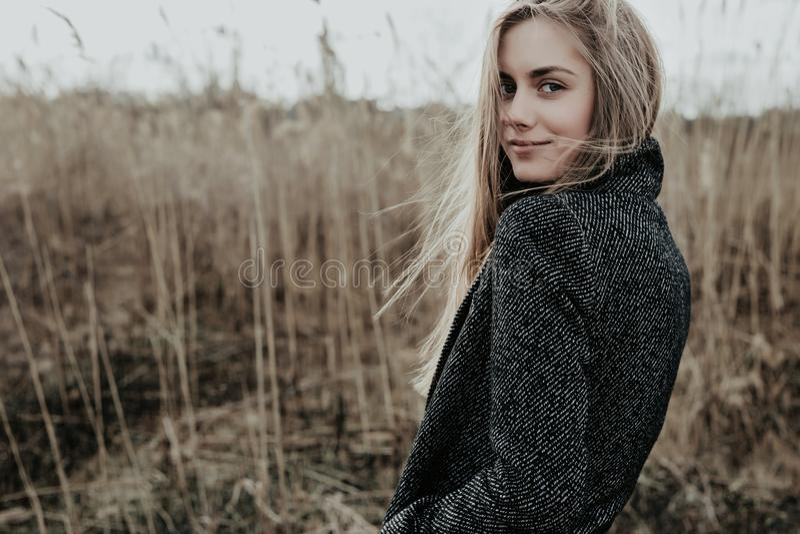 De mooie en jonge vrouw met lang blondehaar kleedde zich in wollaag bekijkend camera over haar schouder en het glimlachen Achterg stock afbeelding
