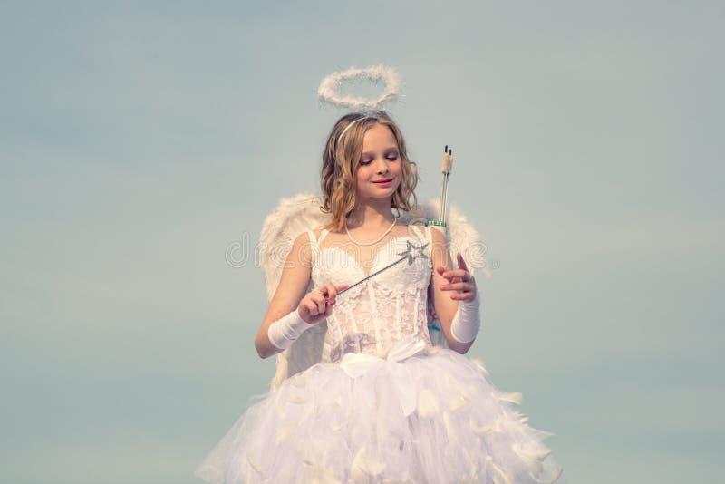 De mooie en leuke jeugd Meisjesengel met halo in witte engelenkleding De Cupido van de valentijnskaartendag Cupido in valentijnsk stock afbeelding