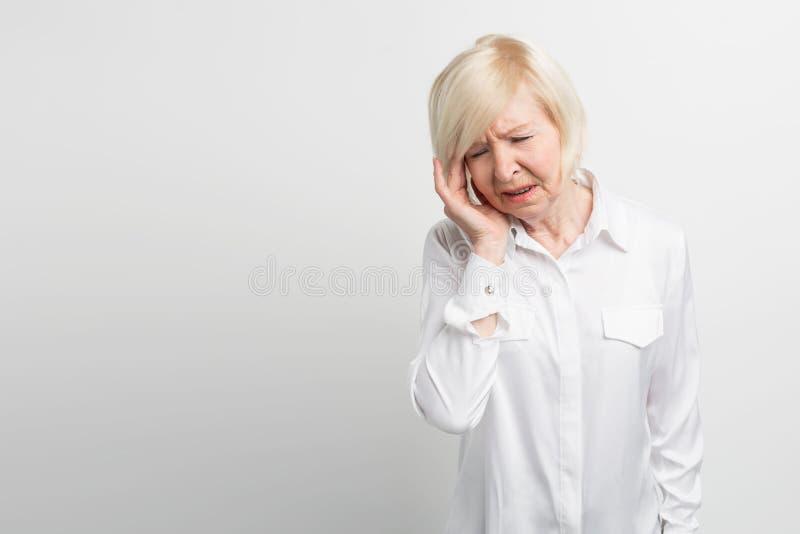 De mooie en rijpe vrouw houdt haar hand dicht bij haar hoofd Zij heeft een hoofdpijn Zij moet een pil nemen om te voelen royalty-vrije stock foto