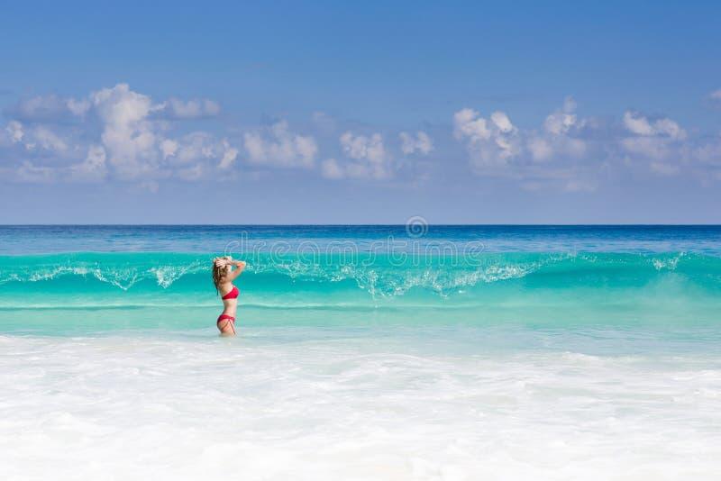 De mooie en sexy blondevrouw in rode bikini, turquise overzees royalty-vrije stock fotografie