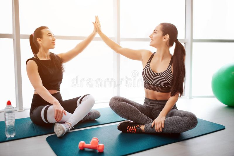 De mooie en well-built jonge vrouwen zitten op matrass in lotusbloem stellen Zij geven hoog-vijf aan elkaar De modellen zijn aanw royalty-vrije stock afbeelding