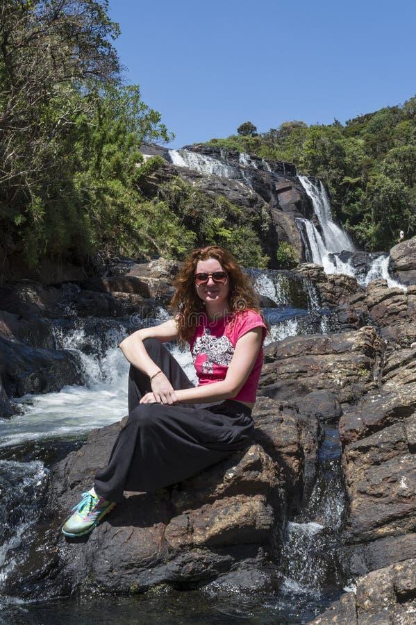 De mooie Europese zitting van de toeristenvrouw op de steen dichtbij de reusachtige waterval stock afbeelding