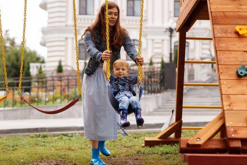 De mooie familie heeft buiten pret Mamma met haar zon die op een schommeling berijden Het mamma speelt met haar weinig zoon op ee royalty-vrije stock afbeelding