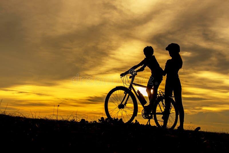 De mooie familie van de silhouetfietser bij zonsondergang over de oceaan Mamma en dochter ontspant de bicycling kou en bij het st royalty-vrije stock afbeelding