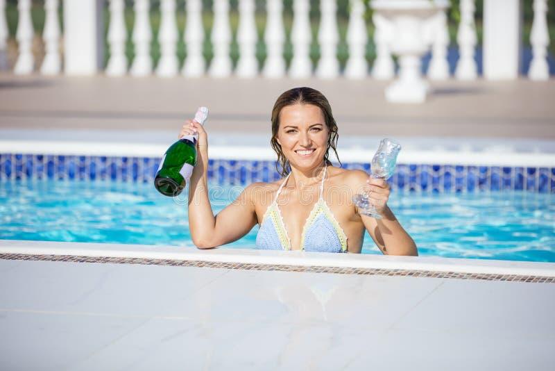 De mooie fles van de vrouwenholding champagne en glazen in pool stock fotografie