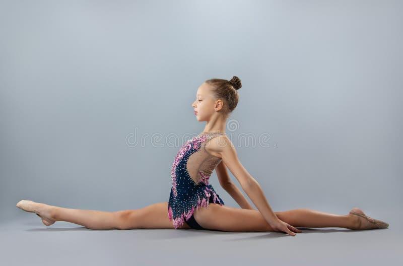 De mooie flexibele turner in sportenuitrusting voert een element van ritmische gymnastiek uit stock afbeeldingen