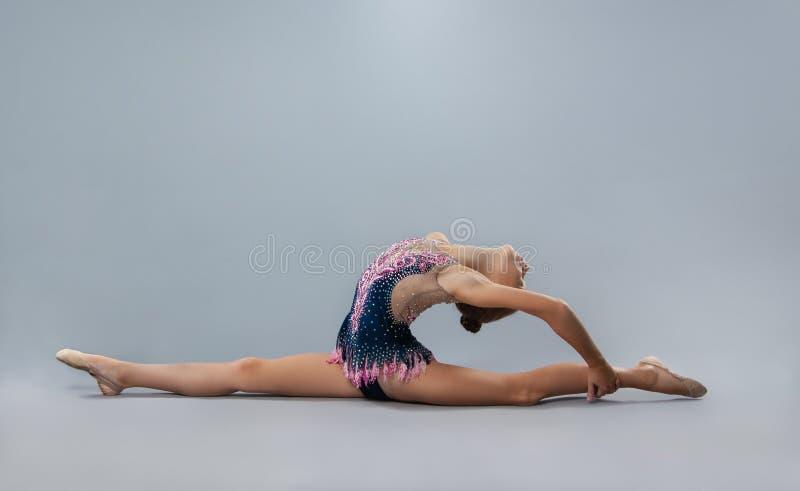 De mooie flexibele turner in sportenuitrusting voert een element van ritmische gymnastiek uit royalty-vrije stock afbeelding