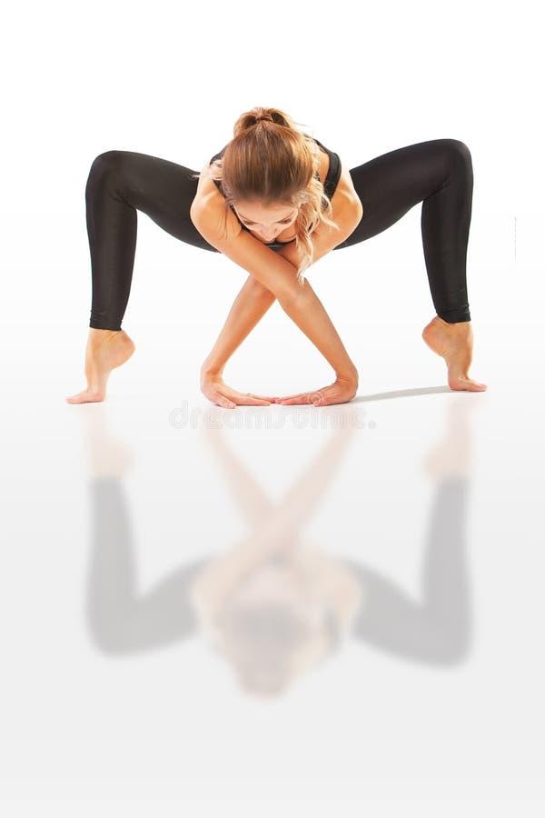 De mooie flexibele vrouw die yoga doen stelt op wit royalty-vrije stock afbeeldingen