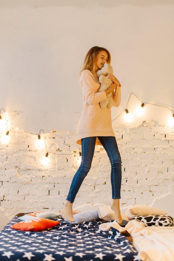 De mooie foto van gemiddelde lengte van het jonge blonde meisje dat de teddybeer koestert en op het bed springt royalty-vrije stock foto
