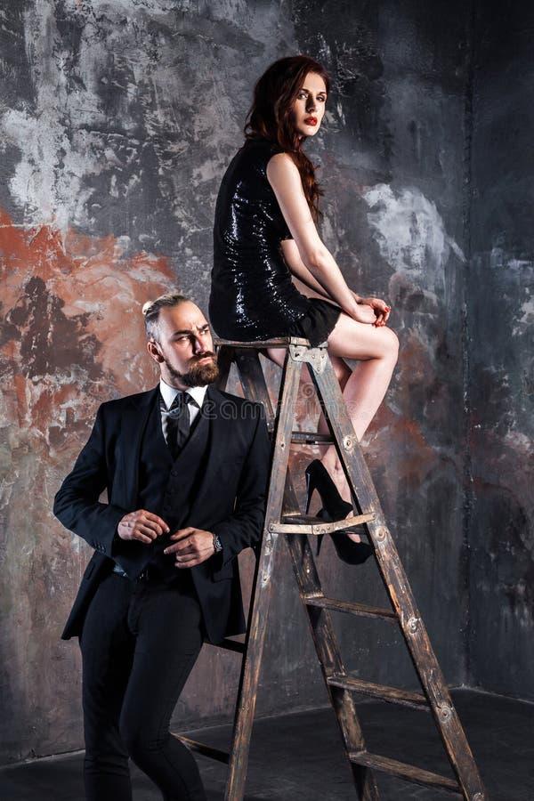 De mooie foxy vrouw, de vearing zwarte kleding en de hiel zitten op trapladder en het bekijken camera Het gebaarde zakenman stell royalty-vrije stock foto's