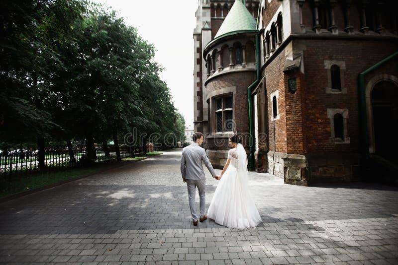 De mooie gang van het jonggehuwdepaar dichtbij oude christelijke kerk stock fotografie