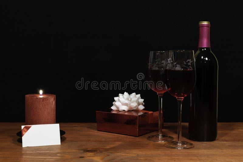 De mooie geëtste wijnglazen en de fles rode wijn, rode kaars, verpakten heden met boog op houten lijst met naamplaatje op dark stock foto