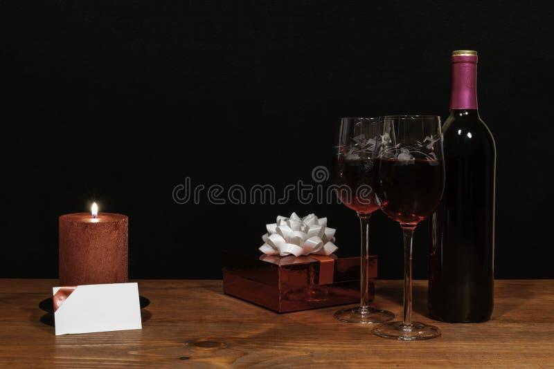 De mooie geëtste wijnglazen en de fles rode wijn, rode kaars, verpakten heden met boog op houten lijst met naamplaatje op dark royalty-vrije stock fotografie