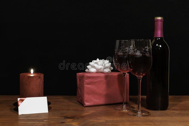 De mooie geëtste wijnglazen en de fles rode wijn, rode kaars, verpakten heden met boog op houten lijst met naamplaatje op dark stock afbeeldingen