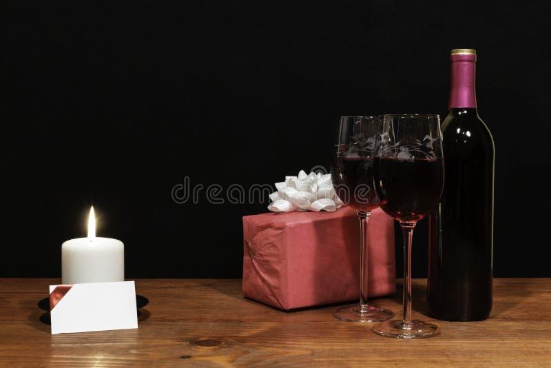 De mooie geëtste wijnglazen en de fles rode wijn, witte kaars, verpakten heden met boog op houten lijst met naamplaatje op dark royalty-vrije stock foto
