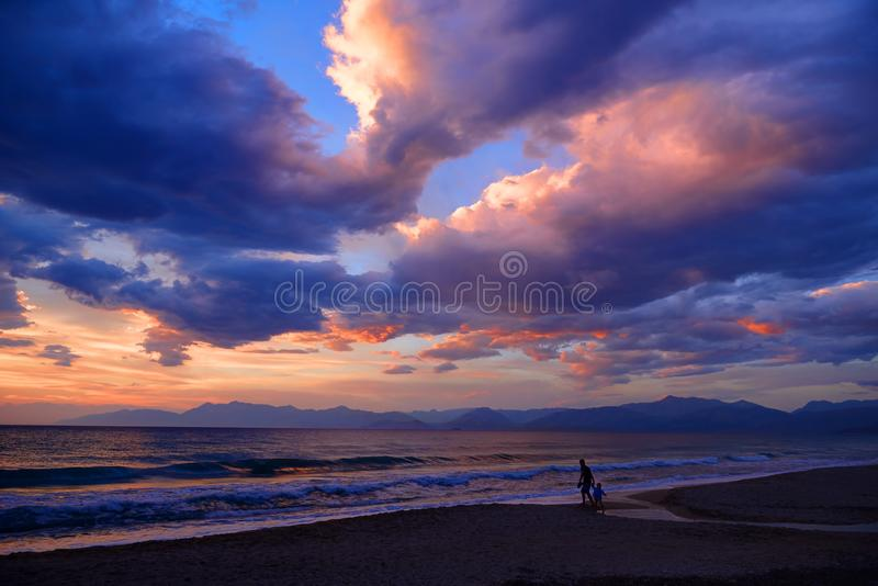 De mooie geheimzinnige dramatische romantische kleurrijke zonsondergang van de zonschemer op Ionische Overzees op zandstrand Kind stock afbeelding