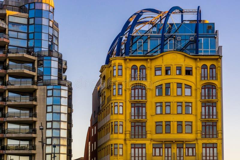 De mooie gele uitstekende bouw met de een andere bouw die heel wat glasvensters, Stadsarchitectuur van Blankenberge heeft, stock afbeeldingen