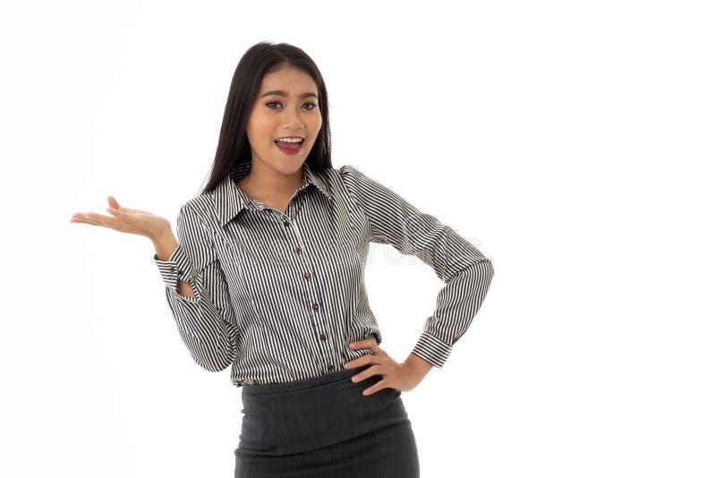 De mooie gelukkige Aziatische jonge dame bevond zich met met de handen in de zij wapens en handheden of toont op product dat op w stock afbeelding