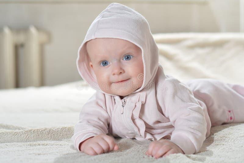 De mooie gelukkige baby na bad bekijkt de camera stock afbeelding