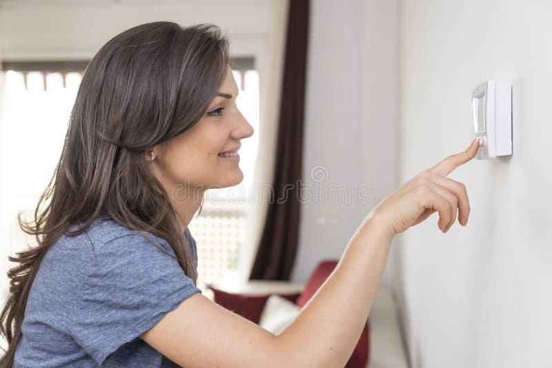 De mooie gelukkige digitale thermostaat van de vrouwendrukknop bij huis