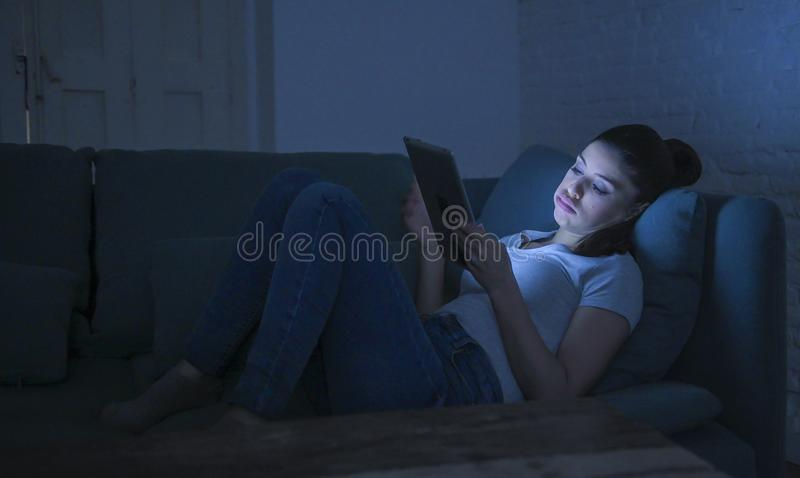 de mooie gelukkige en ontspannen Latijnse vrouwenjaren '30 die op huis liggen gaan liggen laat - nacht gebruikend het digitale ap royalty-vrije stock afbeeldingen