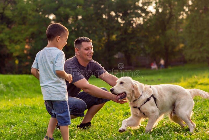 De mooie gelukkige familie heeft pret met golden retriever - Vet royalty-vrije stock foto's
