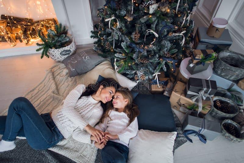 De mooie gelukkige familiemoeder en de dochter met giften rond Kerstmisboom zijn samen thuis op de vloer stock foto