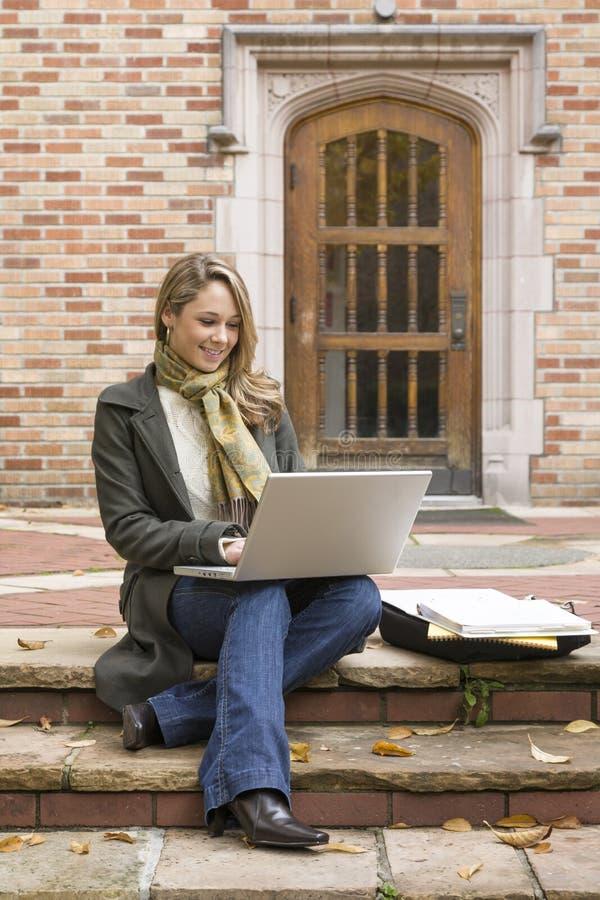 De mooie, gelukkige, glimlachende, vrouwelijke universitaire student die van de vrouwenuniversiteit gebruikend laptop computer op stock afbeelding