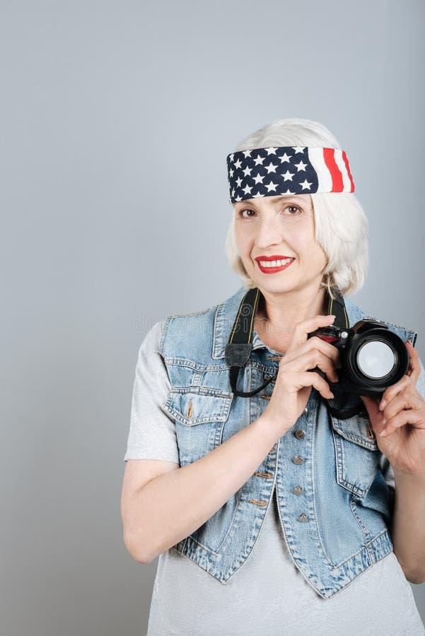 De mooie gelukkige hogere camera van de vrouwenholding royalty-vrije stock afbeelding