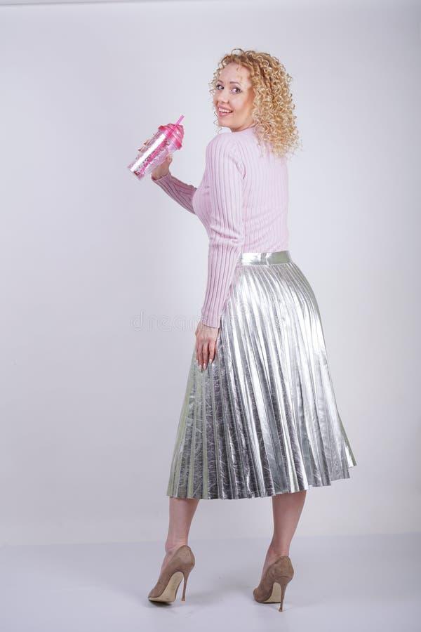 De mooie gelukkige Kaukasische vrouw met krullend blondehaar bevindt zich in een dunne roze gebreide sweater en metaal zilveren g royalty-vrije stock fotografie