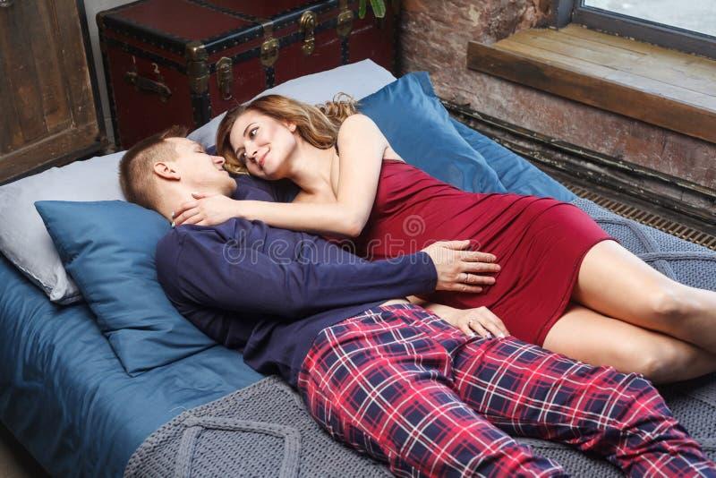 De mooie gelukkige zwangere vrouw en haar echtgenoot in nachtkleding koesteren en kijken aan elkaar terwijl samen binnen het door stock afbeelding
