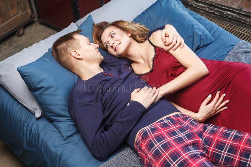 De mooie gelukkige zwangere vrouw en haar echtgenoot in nachtkleding koesteren en kijken aan elkaar terwijl samen binnen het door royalty-vrije stock afbeeldingen