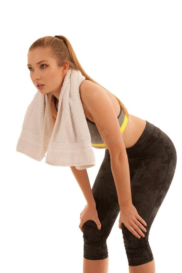 De mooie geschikte vrouw rust na training met handdoek arounf haar die hals over wit wordt geïsoleerd stock foto's