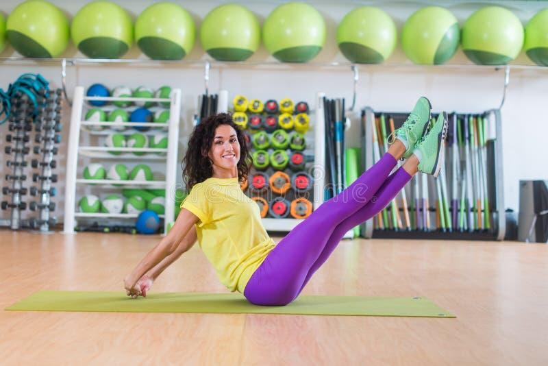 De mooie geschiktheid model het doen zitting van de schaaroefening op vloer die en het rechte benen glimlachen kruisen uncrossing stock afbeelding