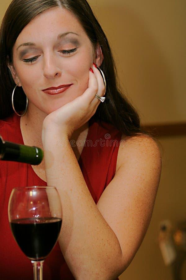De mooie gesloten ogen van de vrouwen gietende wijn royalty-vrije stock afbeelding
