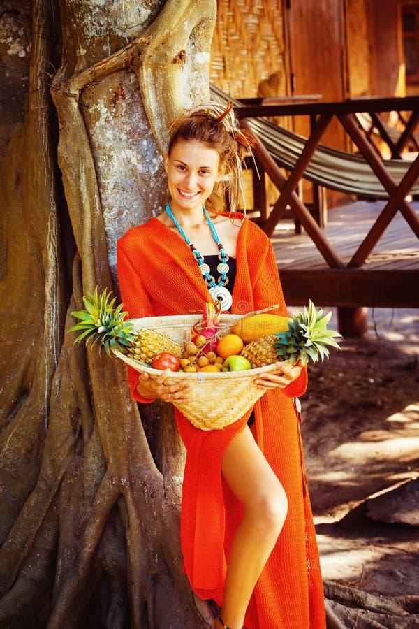 De mooie gezonde jonge vrouw houdt mand van tropische frui stock afbeelding