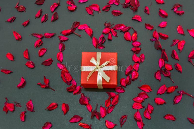 De mooie Gift van de Valentijnskaartendag voor de liefde van het leven in het centrum van hart vormde toenam bloemblaadjes stock afbeelding