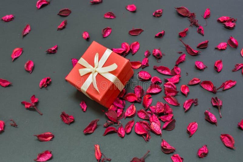 De mooie Gift van de Valentijnskaartendag voor de liefde van het leven in het centrum van roze bloemblaadjes royalty-vrije stock foto