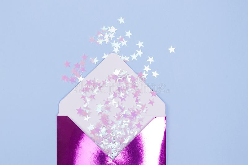 De mooie glanzende envelop met schittert confettien in een vorm meespeelt op een blauwe achtergrond Feestelijk concept stock fotografie