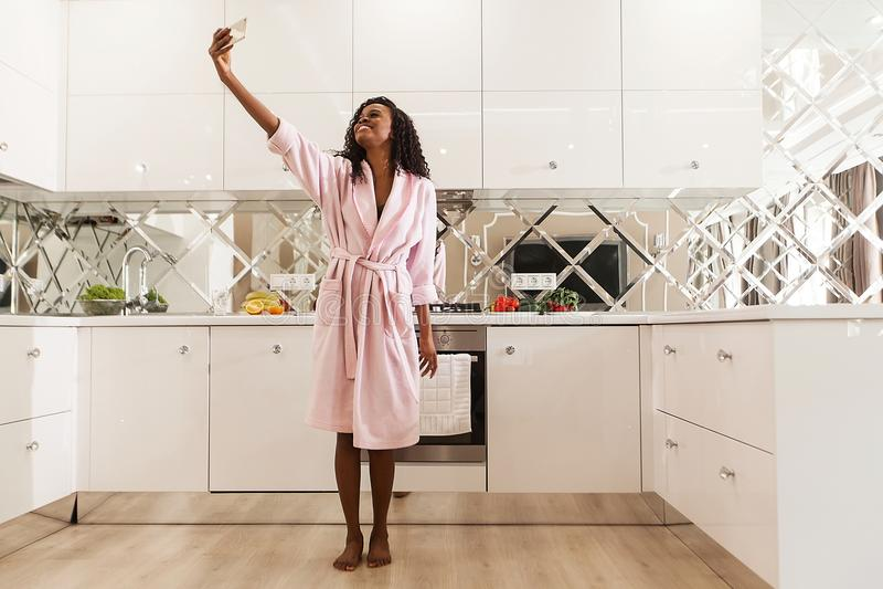 De mooie glimlachende Afrikaanse vrouw met krullend haar in roze badjas neemt selfie op de mobiele telefoon Moderne keuken stock afbeelding