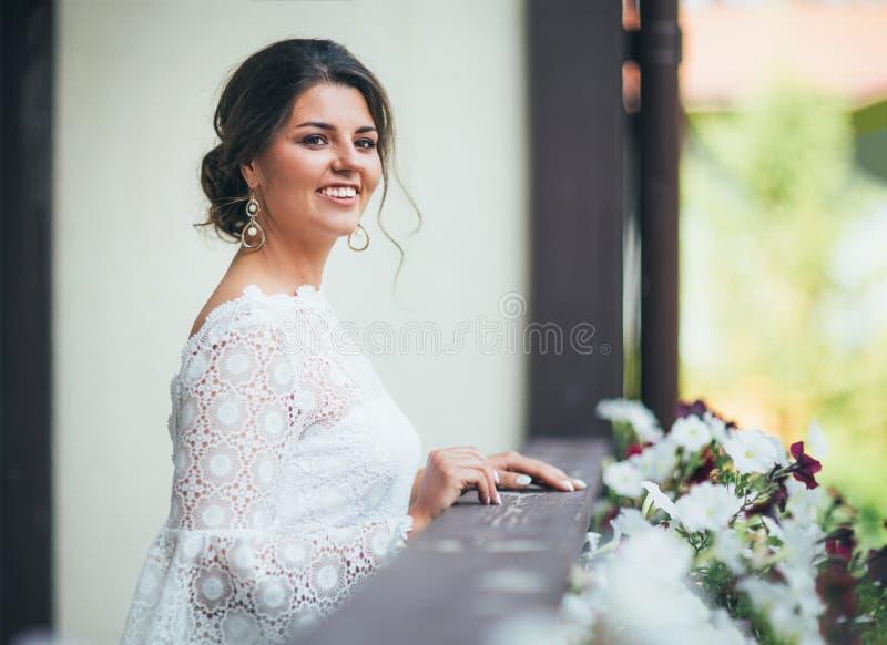 De mooie glimlachende bruid donkerbruine jonge vrouw in witte kantkleding op balkon, sluit omhoog portrai stock foto's