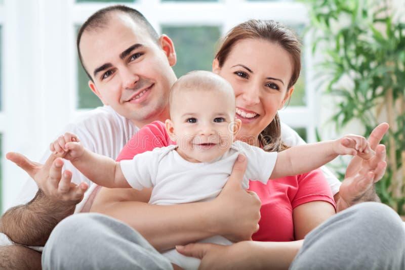 De mooie glimlachende gelukkige familie geniet thuis van stock afbeelding