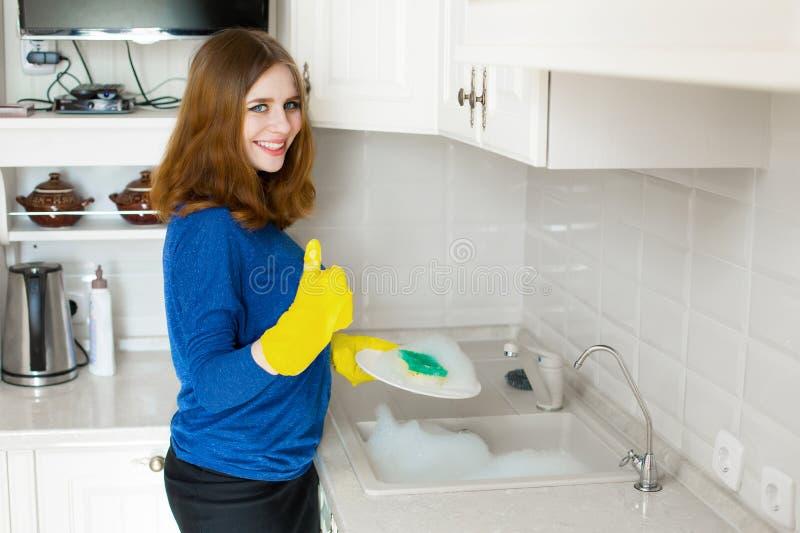 De mooie glimlachende huisvrouw toont duimen op symbool terwijl het wassen van plaat royalty-vrije stock fotografie