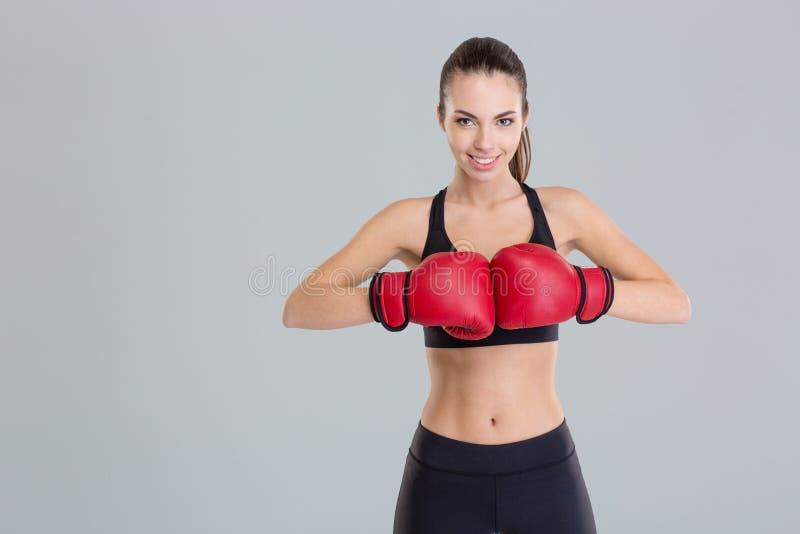 De mooie glimlachende jonge geschiktheidsvrouw draagt rode bokshandschoenen royalty-vrije stock foto