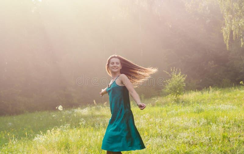 De mooie glimlachende jonge vrouw danst en wervelt op een bloem royalty-vrije stock foto