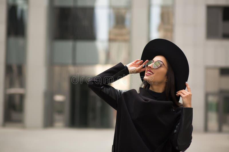 De mooie glimlachende vrouw binnen brimmed wijd zwarte hoed en spiegelzon royalty-vrije stock afbeelding