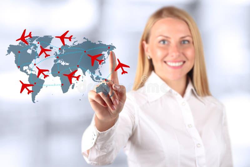 De mooie glimlachende vrouw die een vliegtuig trekken leidt op wereldkaart royalty-vrije stock foto's
