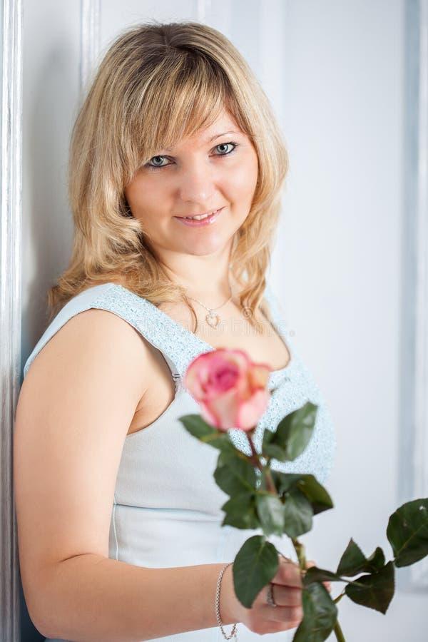 De mooie glimlachende vrouw met nam toe stock fotografie